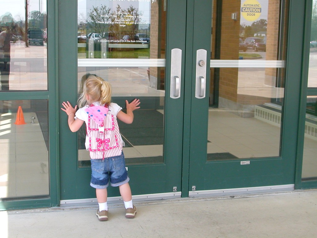 3 year old Maddie looks in to her early childhood class on her first day of school.